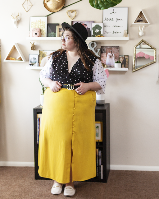 An outfit consisting of a black wide brim hat, a white on black dotted dress with black on white dotted flowy sleeves under a yellow button down midi skirt and white mules.