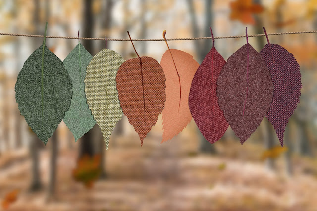 A number of fabric leaf cut outs on a string in front of trees