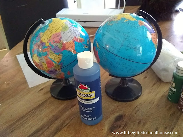 2 globes on table with acyrlic paint ready to be painted as montessori sandpaper and continent globes