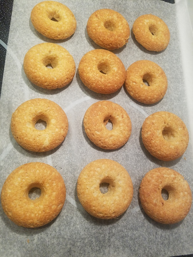 these are a sour cream baked donut cooling on parchment paper