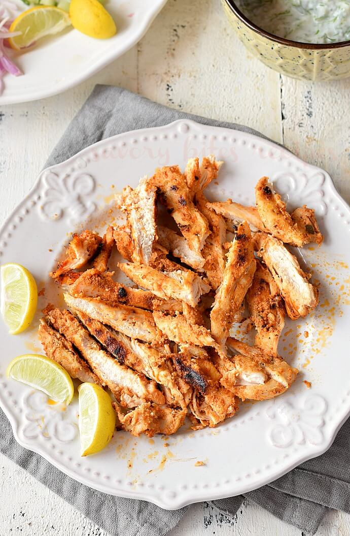 a white plate with grilled shredded chicken