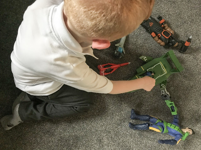 Overhead shot of boy playing with the action figures