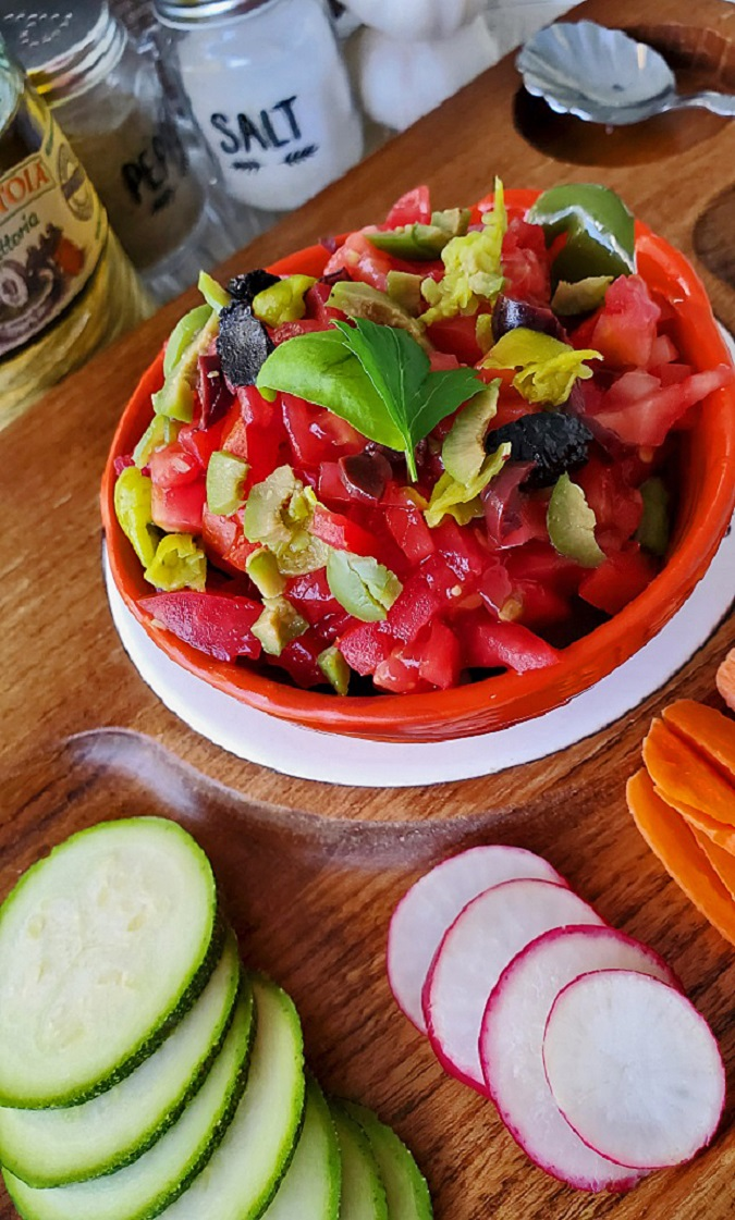 this is fresh vegetables chopped filled in a red bowl with olive oil salt and pepper