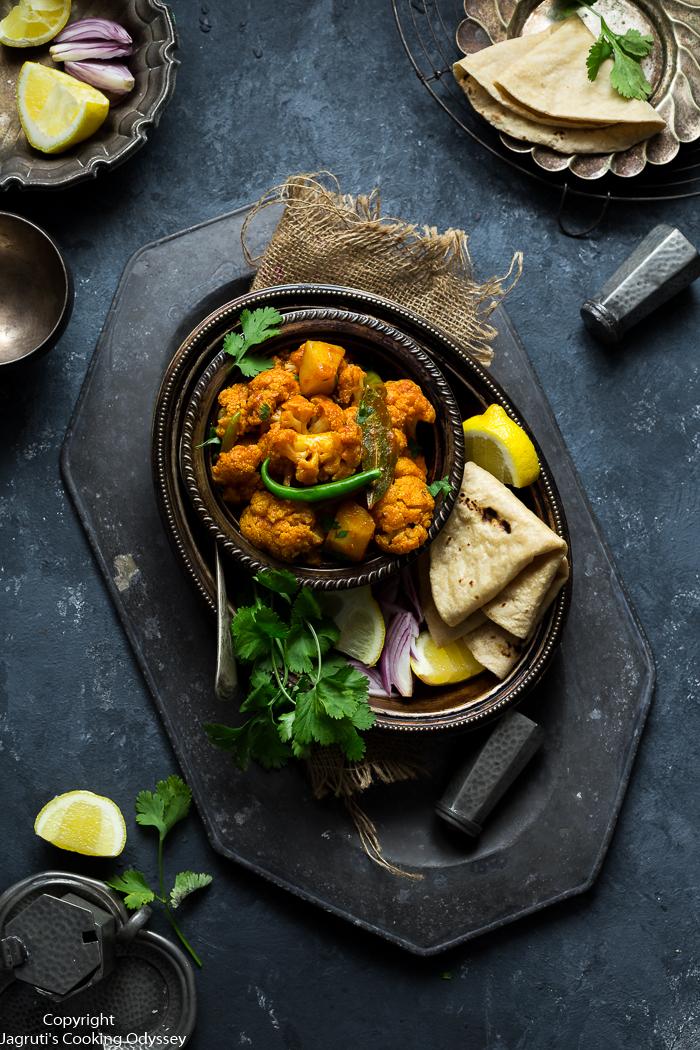Light orange colour aloo gobi served in a metal bowl with roti