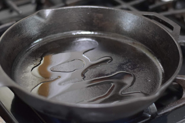 A cast iron pan on the stove with a little oil.