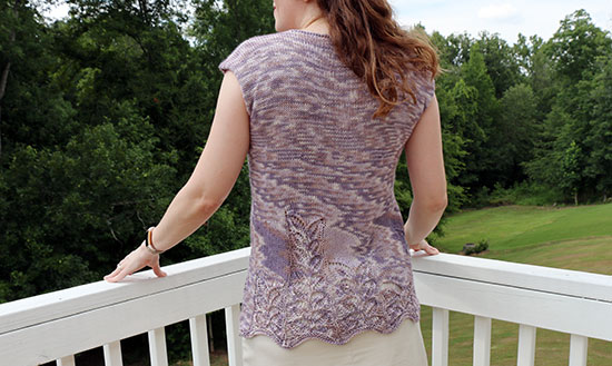 Back view of a woman standing in front of a white rail and green trees wearing a lavender colored sleeveless hand knit top with a lace motif toward the lower hem.