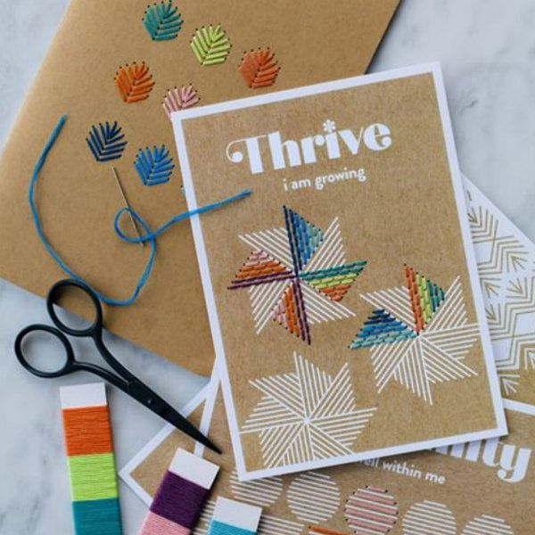 paper stitching cards with threaded needle, floss and small scissors