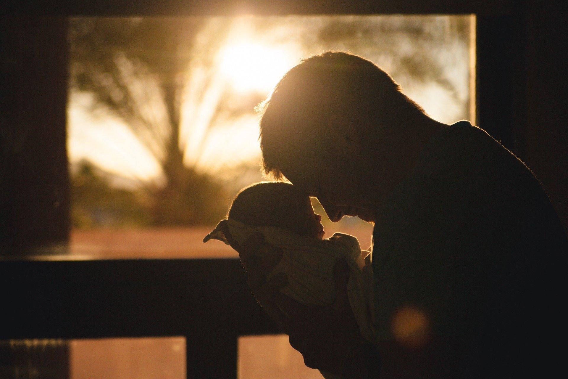 صورة في غروب الشمس لوالد يحتضن طفله بين ذراعيه