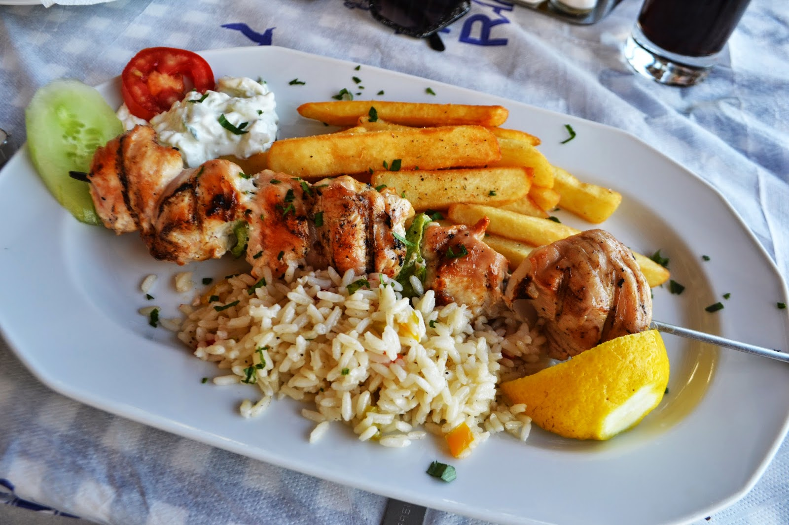 a plate of chicken souvlaki, chips, rice and a small amount of salad