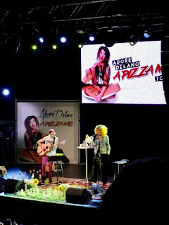 A white rectangular screen with a picture of a blue haired person wearing a black dress with adore delano in white font in a black rectangular strip with a pizza me in red font with a dark square dark brown stage with a woman wearing blonde hair and black jeans with a white jacket on a dark background