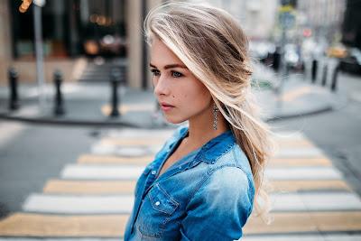 Preciosa Chica Rubia con chaqueta vaquera azul mirando a la nada en la calle