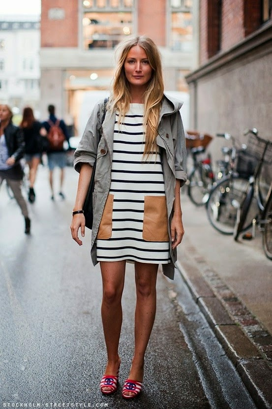a woman wearing a horizontal stripped dress in white and black and chanel open back sandals