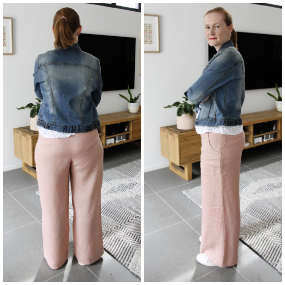 a white lady posing in a pair of pink wide leg pants and a blue denim jacket