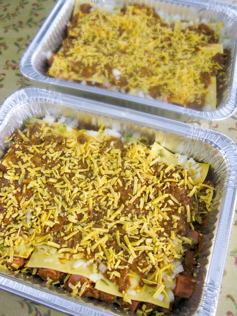 Chili Cheese Hot Dog Bubble Up Bake, buttery cut up pillows of dough and bite size hot dogs layered together with creamy, gooey cheese and chili with beans.  Garnish with your favorite condiments, and you have America's classic Friday night football food rolled up in a casserole.