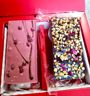 Two rectangular chocolate bars. One pink with long green thin branches on it and red blobs to look like cherry blossoms on it and one brown with with punk and green bits all over it on a bright background
