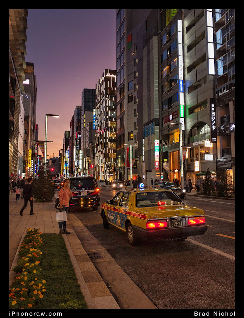Ginza at night with yellow taxi and dusk sky.