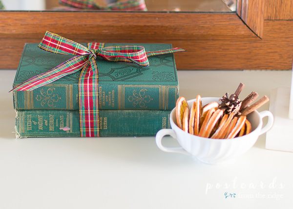 vintage green books with red and green plaid ribbon and orange slices in an old sugar bowl