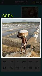 по ступенькам поднимается мужчина на голове которого корзина с солью