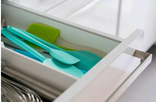 Various kitchen utensils in a white, opened drawer.