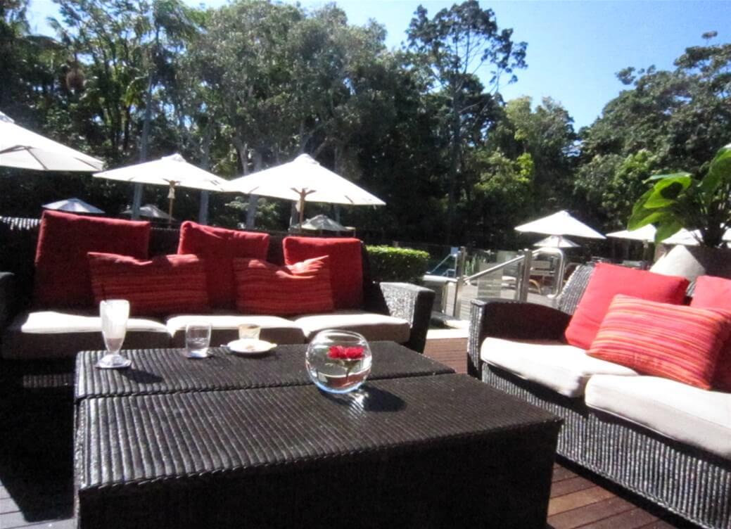 『Byron at Byron』のホテル内にある自然に囲まれた屋外ラウンジの写真