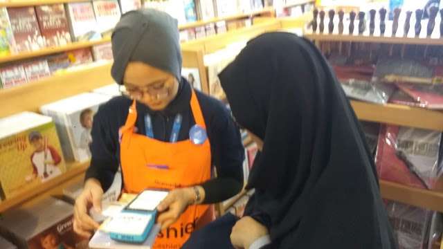 Dian, salah seorang pelanggan toko buku Gramedia mendapatkan layanan Pos Mobile. SPG  dengan membawa mesin cashlez mendatangi konsumen untuk transaksi tidak perlu antri. (dok. windhu).