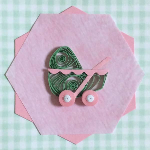 quilled pink and green baby carriage placed on two offset paper hexagons