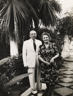 Richard and Alice Neumann standing in a garden, smiling. Black and white.