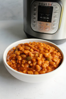 bowl of maple baked beans ready to be served in front of electric pressure cooker