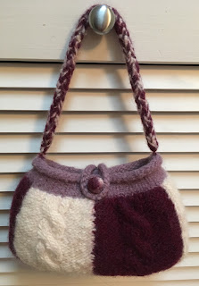 Bag is knitted in multiple colors with cables, icord handle, felt button, and fulled