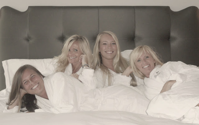 Women in white spa robes lounging on a beautiful bed with crisp white linens at Waldorf Astoria Chicago by Hello Lovely Studio