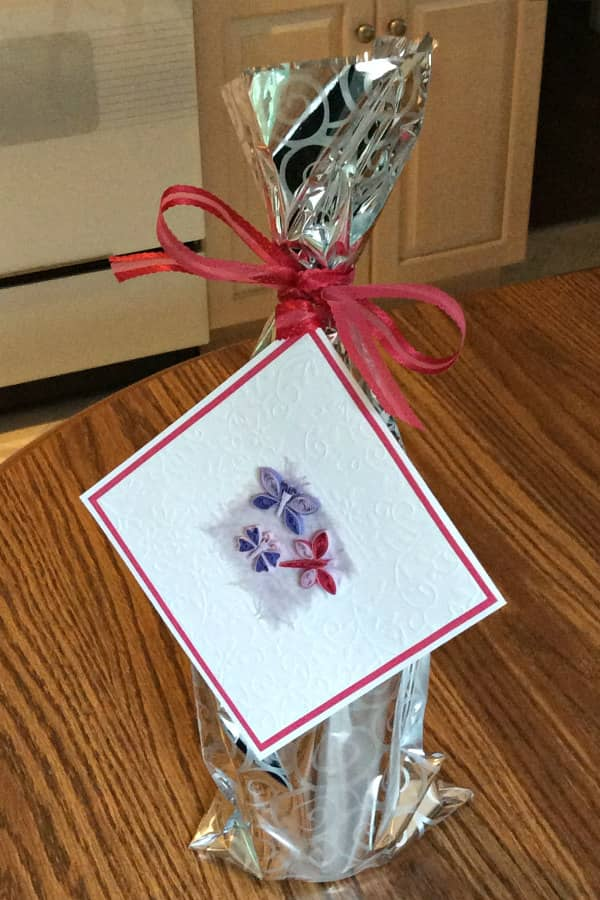 hoge fles gewikkeld in zilver mylar, vastgebonden met roze lint waarop een vierkante kaart met drie quilled vlinders is bevestigd