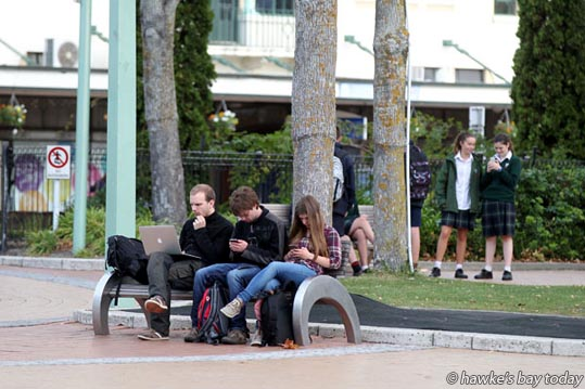 Enjoying the warm cloudy weather, probably accessing the free wi-fi for their laptop, digital devices, mobile phones, cellphones, pictured in the Hastings CBD, Hastings. photograph