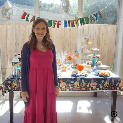 awayfromtheblue Instagram | birthday part host outfit pink tiered midi dress with purple cardigan birthday party decorations space