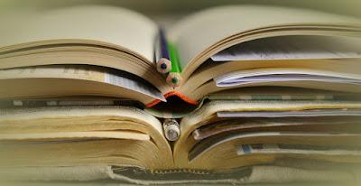 livros empilhados com lápis e canetas sobre eles