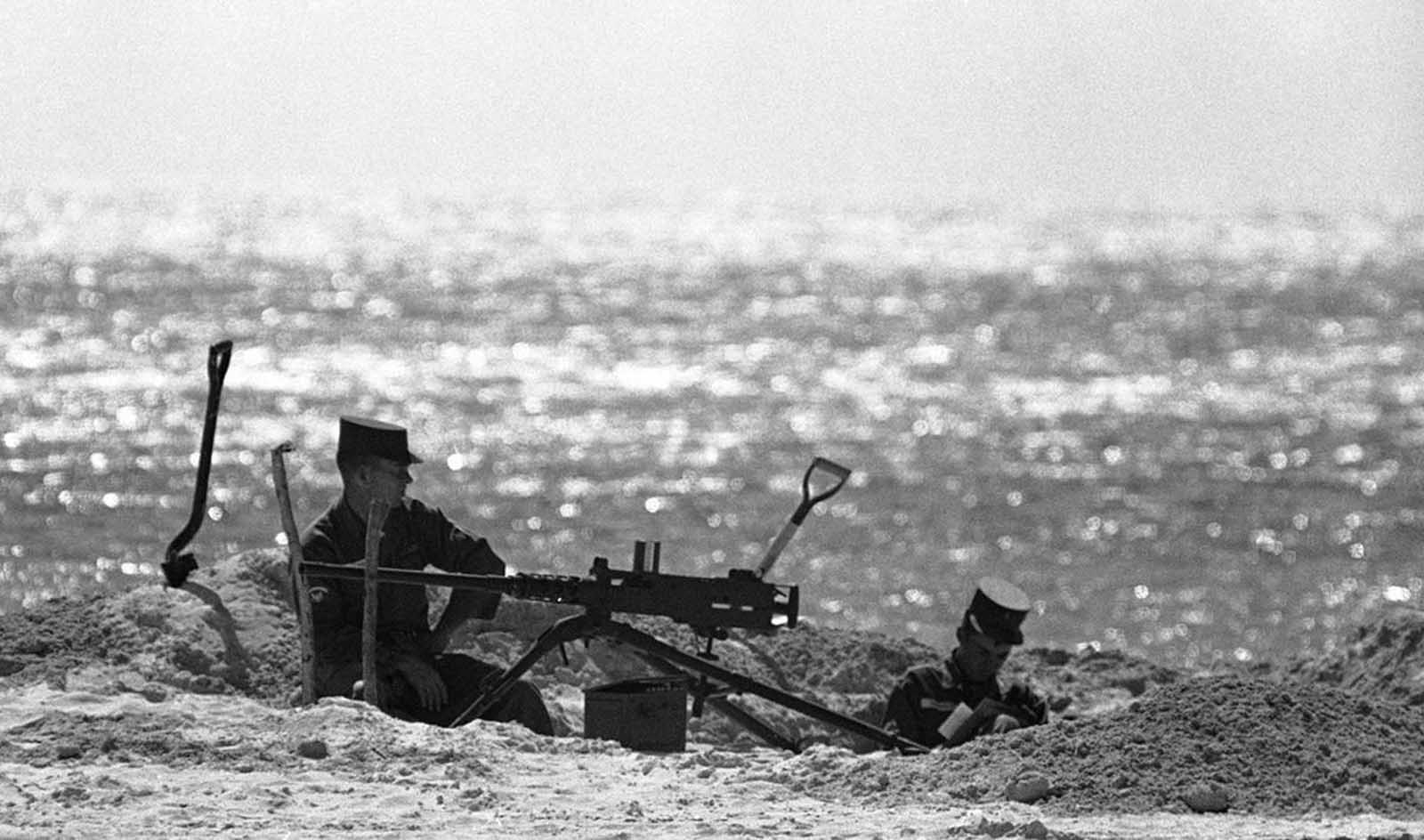 Two soldiers sit in a sandy dugout beside a machine gun hold position on a beach on Key West, Florida, on October 27, 1962.