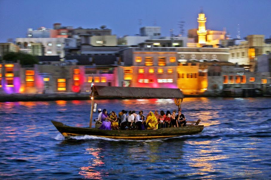 In this Thursday, May 29, 2014 photo, tourists and residents cross the creek waters which cuts through the heart of the city, on a traditional abra, or taxi boat, in Dubai, United Arab Emirates. From early morning to late evening the creek is abuzz with daily commuters and tourists riding in abras, the wooden boats that have been used for more than a century and are still built by hand nearby. The 25-cent passage from one bank to the other is one of the only bargains left in a city where much of the population is expatriates lured to the Gulf emirate by job opportunities.