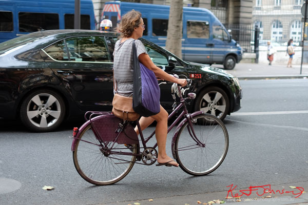 Woman on a purple bike with two bags. Paris photos by Kent Johnson for Street Fashion Sydney.
