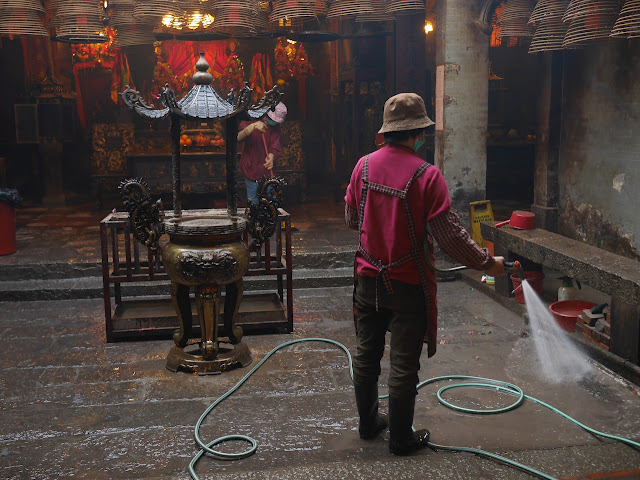 woman spraying water with a hose to clean the Man Mo Temple in Tai Po, Hong Kong