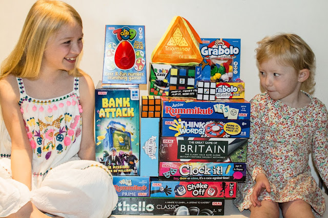 A huge pile of John Adams Ideal family games on a table between 2 children