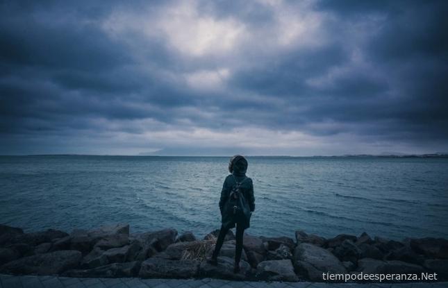 Mujer observando en mar después de la tormenta