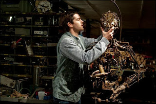 Jim Sturgess as Virgil's gadget man friend Robert, works to repair the automaton in The Best Offer, Directed by Giuseppe Tornatore