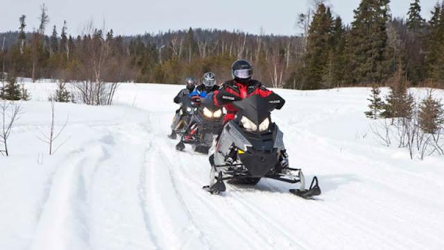 single file snowmobile riders