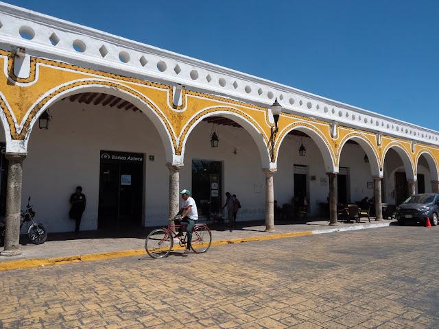 Hombre en bici pasando frente a los arcos de la plaza en Izamal