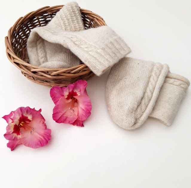 A pair of cream knitted cable socks against a white background.  One of the socks is in a small basket.  There are two pink Gladioli flowers in the foreground