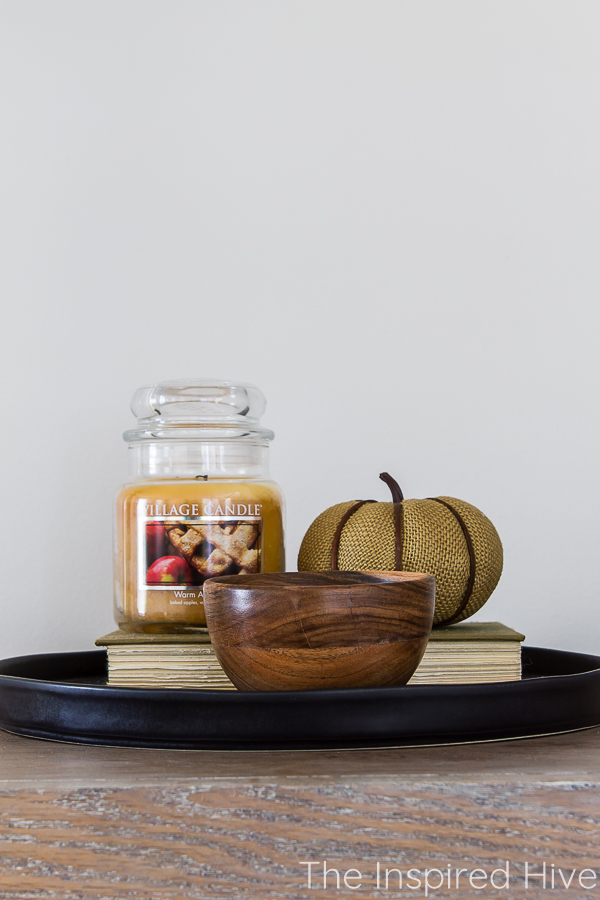 Simple fall vignette with book, candle, pumpkin, and wooden bowl on black ceramic tray