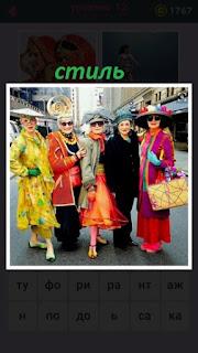 на улице стоит группа людей и каждого свой стиль одежды