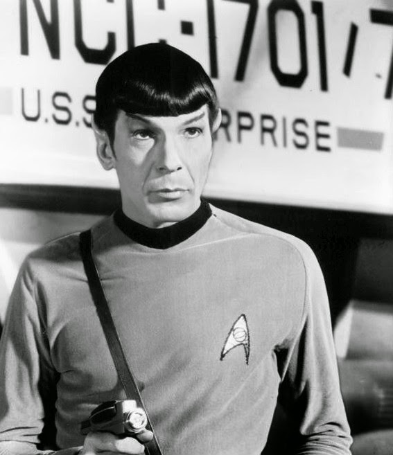 Black and white photo of Mr. Spock pointing a phaser.