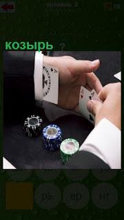 мужчина за столом в казино прячет в рукаве козыри карточные