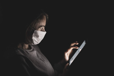 A woman wearing a mask and scrolling on a cell phone