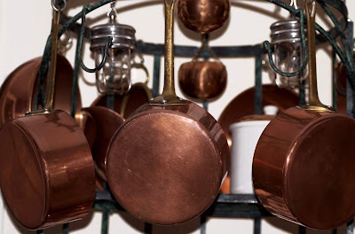 A bunch of copper pots hanging from hooks on an iron pot-older.